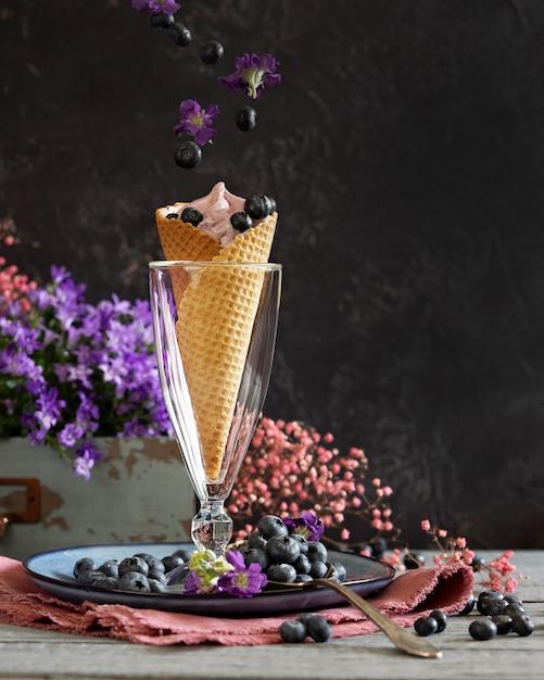 Blaubeerbeeren in einer waffelschale umgeben durch purpurrote blumen und beeren. sommerthema. levitation Premium Fotos