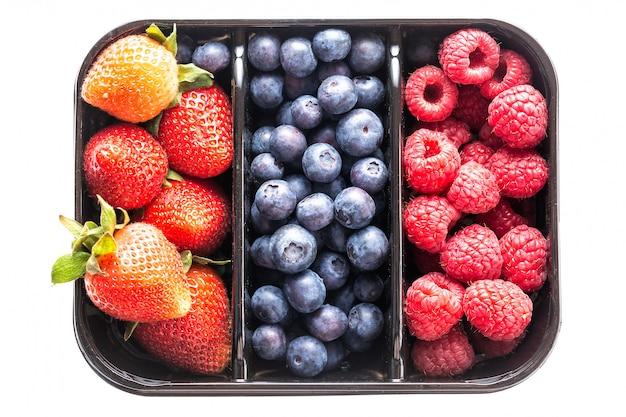 Blaubeeren, erdbeeren und himbeeren in einem kasten lokalisierten o Premium Fotos