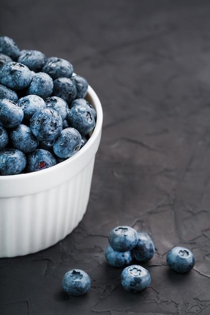 Blaubeeren in einer weißen tasse auf einem schwarzen strukturierten hintergrund Premium Fotos