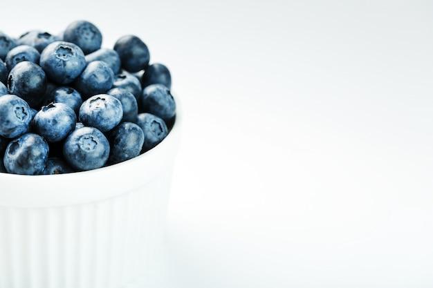 Blaubeeren in einer weißen tasse auf einem weißen hintergrund lokalisiert Premium Fotos