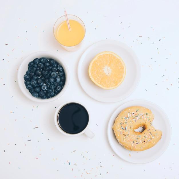 Blaubeeren; kaffeetasse; halbierte orange; saft und donut mit bunten streuseln auf weißem hintergrund Kostenlose Fotos