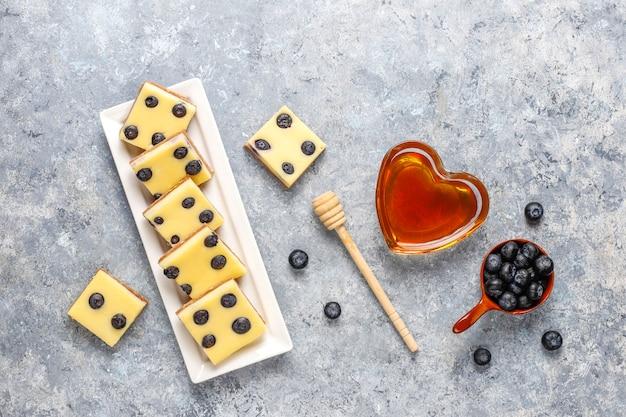 Blaubeerkäsekuchenriegel mit honig und frischen beeren Kostenlose Fotos