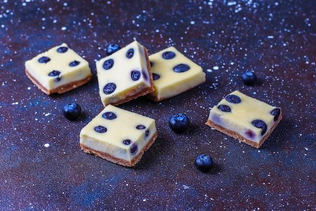 Blaubeerkäsekuchenriegel mit honig und frischen beeren. Kostenlose Fotos