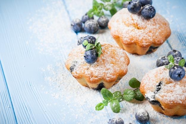 Blaubeermuffin. selbst gemachter gebackener kleiner kuchen mit blaubeeren, frische beeren, minze auf hölzernem hintergrund. Premium Fotos
