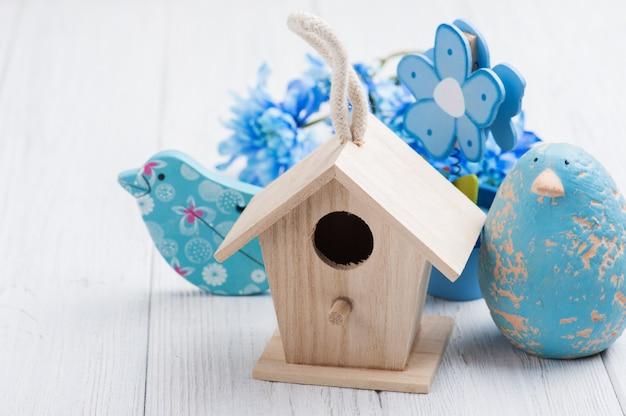 Blaue blumen, spielzeugvögel und vogelhaus Premium Fotos