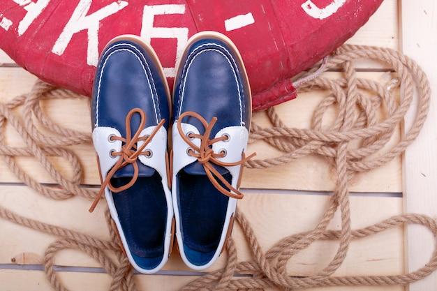 Blaue bootsschuhe auf hölzernem nahem rettungsring und seil. ansicht von oben. Premium Fotos