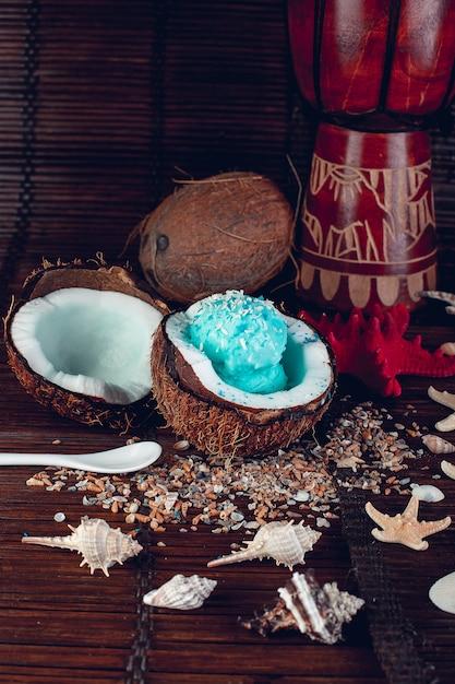 Blaue eiscreme in der kokosnussschüssel nahe sand, muscheln, starfish. Premium Fotos