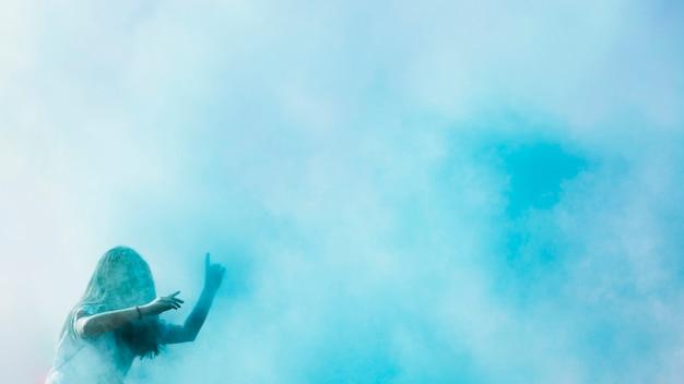 Blaue holi farbexplosion über dem tanzen der jungen frau Kostenlose Fotos