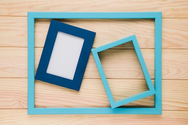 Blaue leere rahmen auf hölzernem hintergrund Kostenlose Fotos
