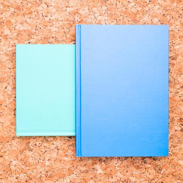 Blaue notizbücher auf hölzernem schreibtisch Kostenlose Fotos