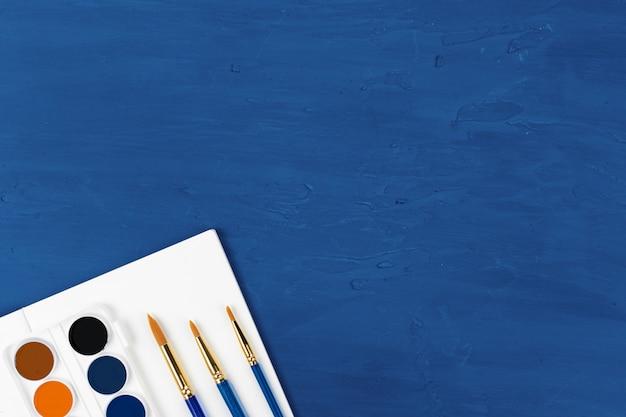Blaue pinsel auf klassischem blauem hintergrund, ansicht von oben Premium Fotos
