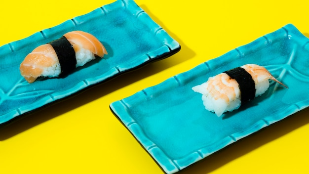 Blaue platten mit sushi auf einem gelben hintergrund Kostenlose Fotos