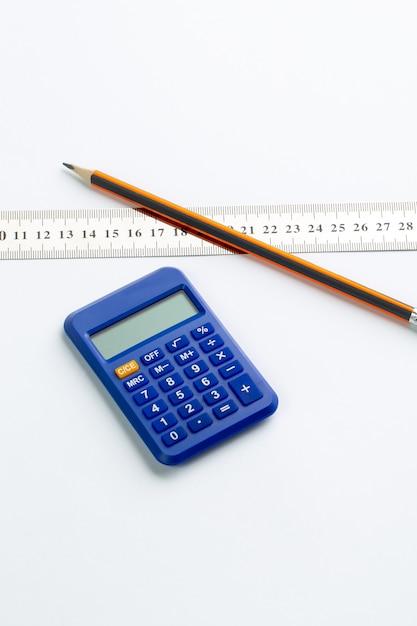 Blaue taschenrechner-buchhaltungshand verwenden zusammen mit graphitstift und transparentem lineal auf weißer wand Kostenlose Fotos
