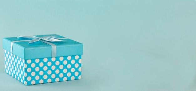 Blaue tupfen-geschenkbox mit schleife auf blauem hintergrund kopieren sie den raum Premium Fotos