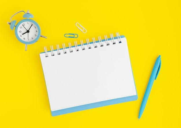 Blaue uhr, notizbuch leer und stift auf gelbem hintergrund. deadline-konzept, modell Premium Fotos