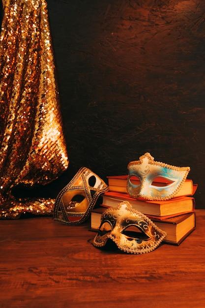 Blaue und goldene masken mit weinlesebüchern und funkelnpaillettengewebe auf hölzernem schreibtisch Kostenlose Fotos
