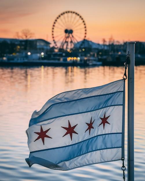 Blaue und weiße flagge mit sternen mit riesenrad und gebäuden hinter einem see im hintergrund Kostenlose Fotos