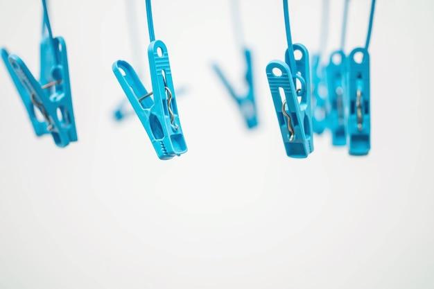 Blaue wäscheklammer der nahaufnahme auf unscharfem strukturiertem hintergrund des weißzements Premium Fotos