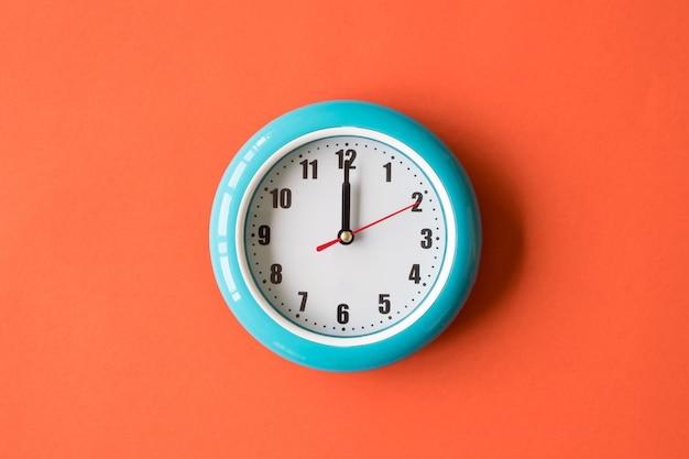 Blaue wanduhr auf orange hintergrund Premium Fotos