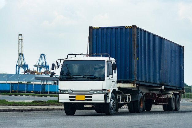 Blauer container-lkw der fracht in schiffshafen logistics transportindustrie im hafengeschäftskonzept. Premium Fotos
