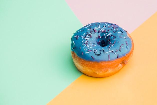 Blauer donut auf farbigem hintergrund Kostenlose Fotos