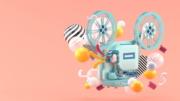 Blauer filmprojektor inmitten bunter kugeln auf rosa. 3d rendern. Premium Fotos