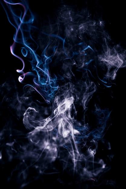 Blauer gewellter rauch auf schwarzem hintergrund Kostenlose Fotos