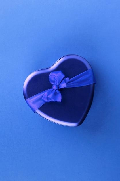 Blauer herzförmiger kasten mit band auf blauem hintergrund Premium Fotos