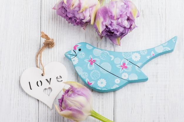 Blauer hölzerner vogel mit purpurroten tulpen und weißem herzen Premium Fotos