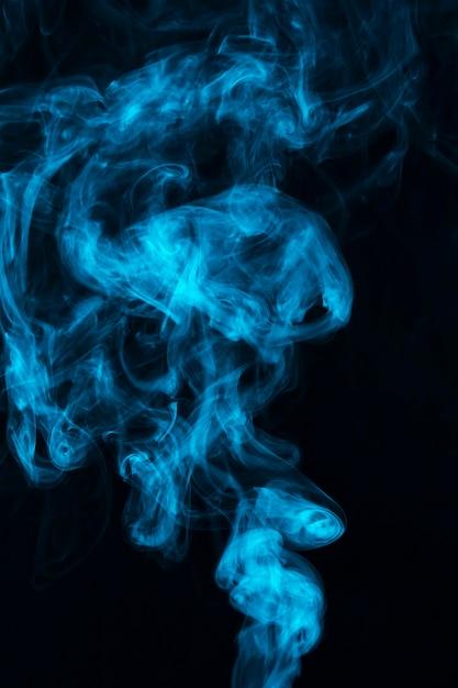 Blauer rauch des dampfes verbreitete gegen schwarzen hintergrund Kostenlose Fotos