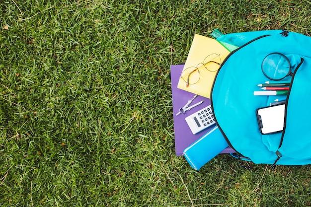 Blauer rucksack mit briefpapier und smartphone Kostenlose Fotos