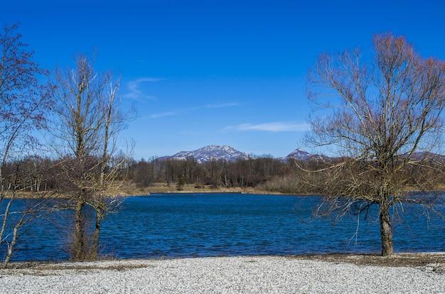 Blauer see mit wäldern und bergen während des tages Kostenlose Fotos