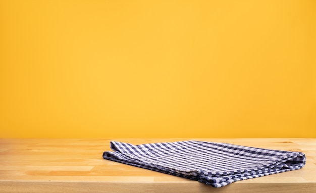 Blauer stoff stoff auf holztischplatte auf gelbem wandhintergrund Premium Fotos