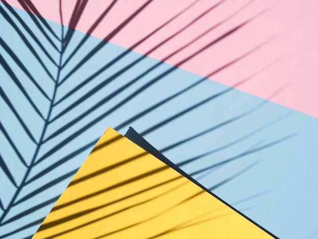 Blauer und rosafarbener hintergrund mit einem blattschatten und einem gelben freien raum Kostenlose Fotos