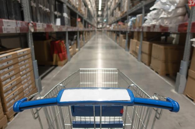 Blauer warenkorb mit unscharfer ansicht des lagerinnenraums mit produkt auf regalen im kaufhauseinkaufszentrum-mittelhintergrund Premium Fotos