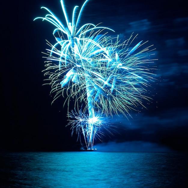 Blaues buntes feiertagsfeuerwerk auf dem schwarzen himmelhintergrund. Premium Fotos