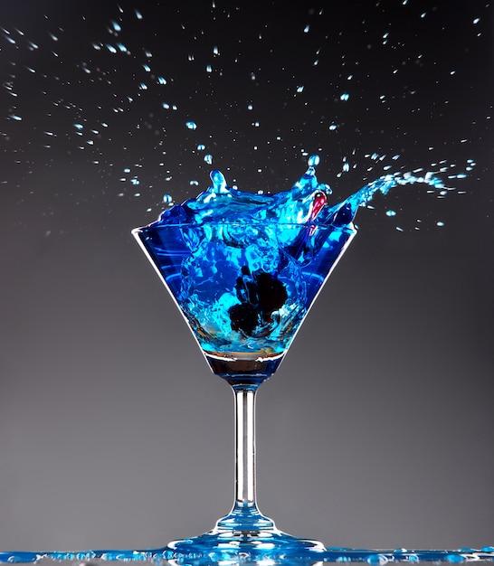 Blaues cocktail, das auf dunklem hintergrund spritzt Premium Fotos