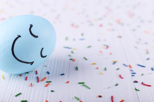 Blaues ei mit gemaltem lächeln glückliche ostern-grußkarte. Premium Fotos