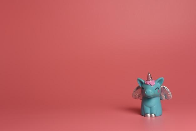 Blaues einhorn mit silbernen flügeln und rosa haaren auf einem rosa hintergrund Premium Fotos