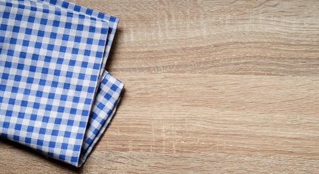 Blaues farbgewebe überprüfte tischdecke auf hölzerner beschaffenheits-tischplatte der weinlese in der küche Premium Fotos