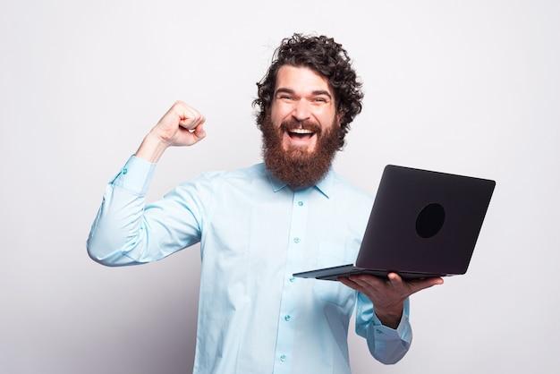 Blaues hemd des bärtigen mannes, der laptop hält und sieg über weiße wand feiert Premium Fotos