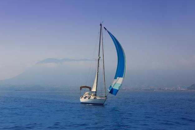 Blaues meer mit segelbootsegeln in einer nebeligen küste Premium Fotos