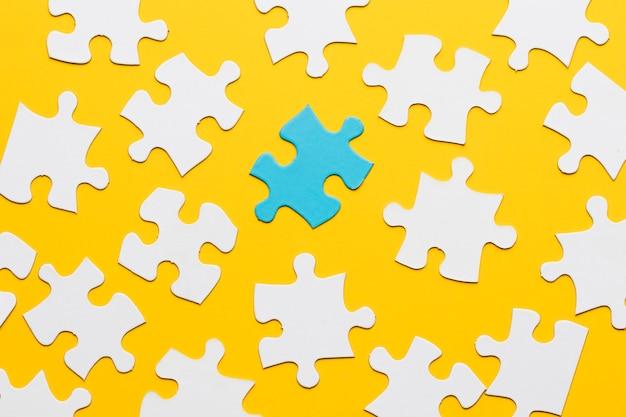 Blaues puzzlespiel mit weißem puzzlestück auf gelbem hintergrund Kostenlose Fotos