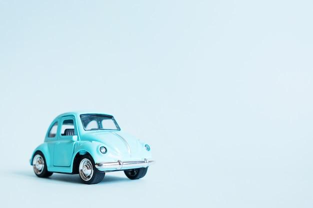 Blaues retro- spielzeugauto auf blau Premium Fotos