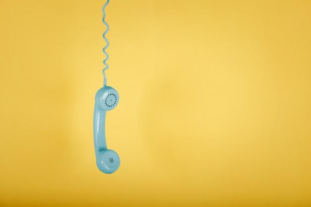 Blaues weinlese-telefon, das auf gelbem raum hängt Premium Fotos
