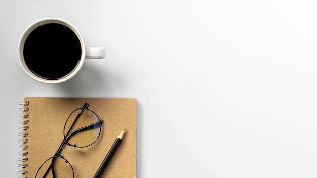 Bleistift, kaffeetasse und tagebuchbuch am weißen schreibtisch. - konzept von zu hause aus arbeiten. Premium Fotos