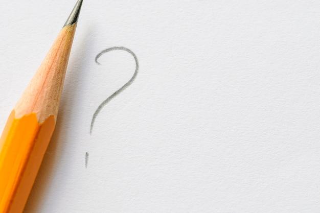 Bleistift neben fragezeichen auf weißem papier Premium Fotos