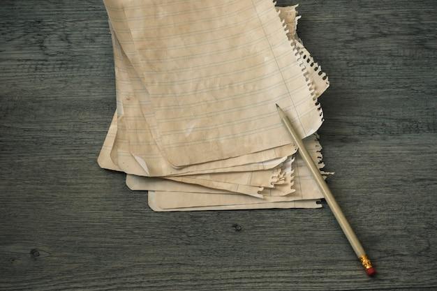 Bleistift und liniertes papier auf hölzerner tischplatte Kostenlose Fotos