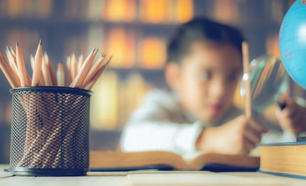 Bleistifte auf einem holztisch und ein asiatisches kind, das fleißig ist, sitzt an einem schreibtischhintergrund. Premium Fotos