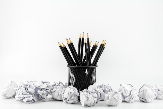 Bleistifte im korb und in zerknittertem papierball auf einer weißen tabelle. - arbeits- und geschäftsideenkonzept. Premium Fotos